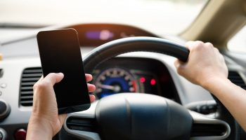 person-holding-black-smartphone-and-vehicle-steering-wheel-1028742